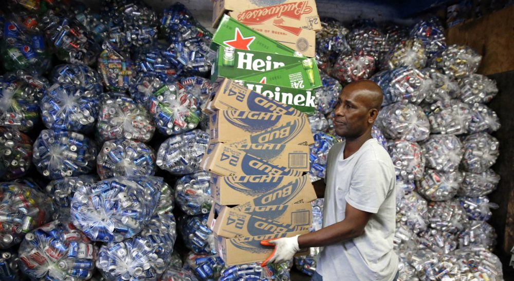 """Jimmy Tingle: """"I'm supporting the expanded Bottle Bill to include plastic water bottles and sports drinks, because it's good for the environment, saves energy and puts money back into the pockets of consumers."""" Pictured: Sorting bottles and cans at a redemption center in the East Boston, Tuesday, Sept. 30, 2014. If approved on Nov. 4, a ballot measure would expand the state's law by adding 5-cent deposits to most non-alcoholic and non-carbonated beverage containers. (Michael Dwyer/ AP)"""