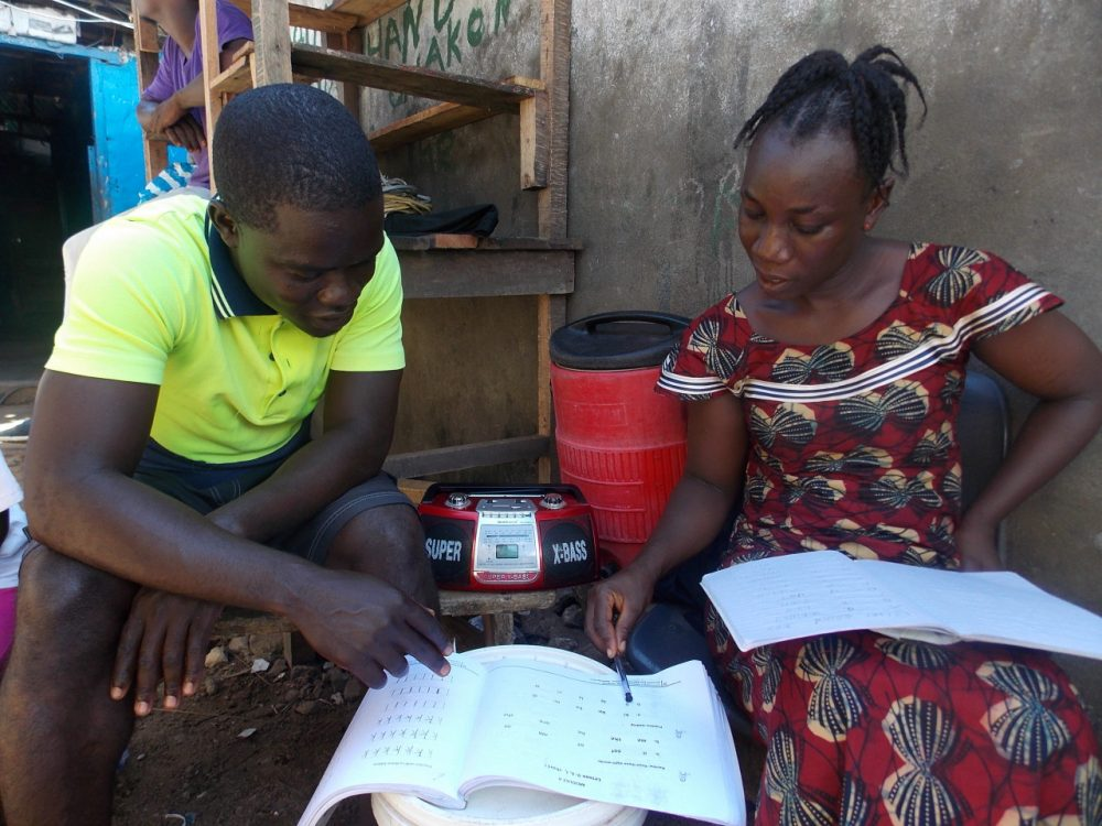 "Kebbeh Sumo and her facilitator, or ""study buddy,"" Francis Mulbah, work on reading and writing in the EDC-USAID workbook as the class broadcasts on the radio that sits between them. In Liberia, education leaders refer to out-of-school ""youth"" as anyone between the ages of 13 and 35 who has never attended school or lost out on schooling, in many cases due to the long civil war.  (Courtesy EDC)"