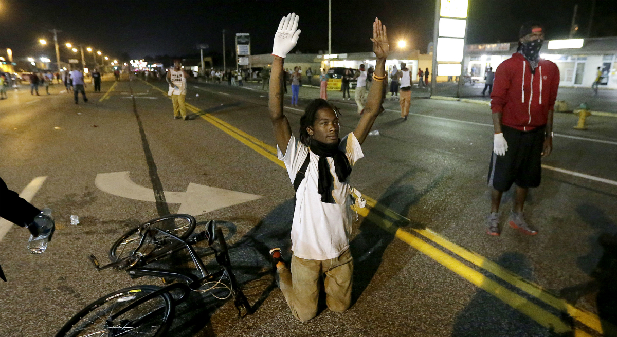 Barbara Beckwith on the challenge of taking action toward a goal that may never be reached. In this photograph, a man holds his hands up in the street after a standoff with police Monday, Aug. 18, 2014, during a protest for Michael Brown, who was killed by a police officer Aug. 9 in Ferguson, Mo. (Charlie Riedel/AP)