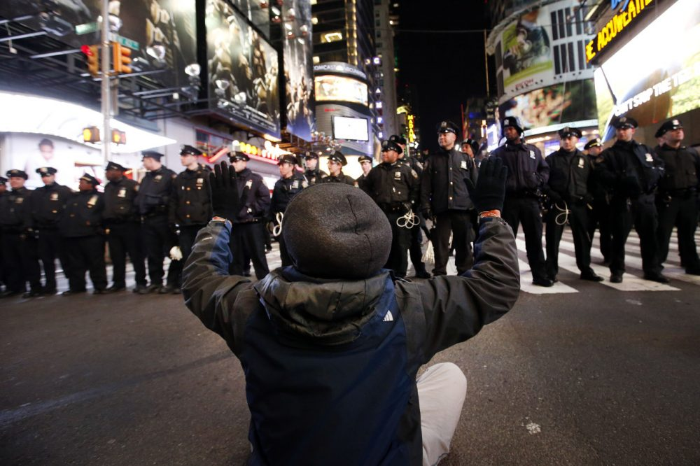 A protester sits in the road while rallying against a grand jury's decision not to indict the police officer involved in the death of Eric Garner encountering a line of police as they make their way west on 42nd Street near Times Square, Thursday, Dec. 4, 2014, in New York. (Jason DeCrow/AP)
