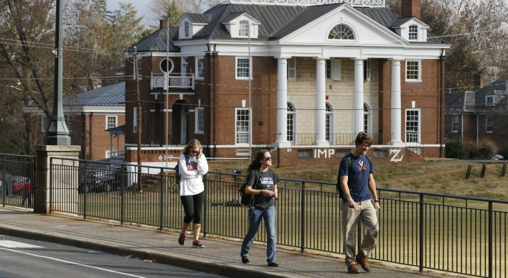 In this photo, University of Virginia students walk to campus past the Phi Kappa Psi fraternity house at the University of Virginia in Charlottesville, Va. Rolling Stone is casting doubt on the account it published of a young woman who says she was gang-raped at a Phi Kappa Psi fraternity party at the school, saying there now appear to be discrepancies in the student's account. (Steve Helber/AP)