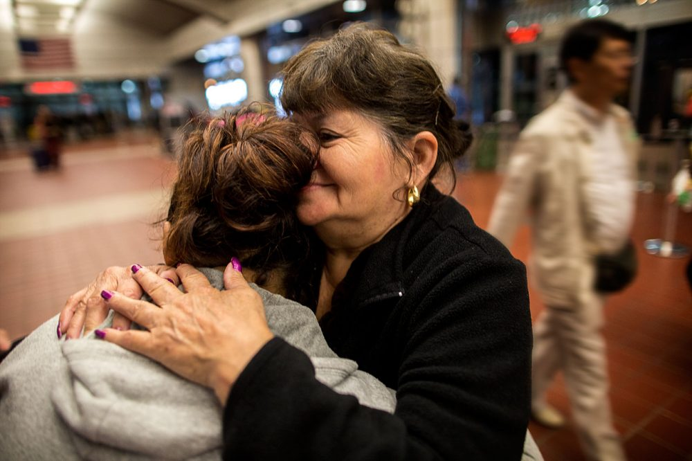Lisette, left, is seeking asylum in the U.S. She fled El Salvador, with a daughter, on July 12, and arrived at Boston's South Station, where she was embraced by her aunt, on Oct. 7. (Jesse Costa/WBUR)
