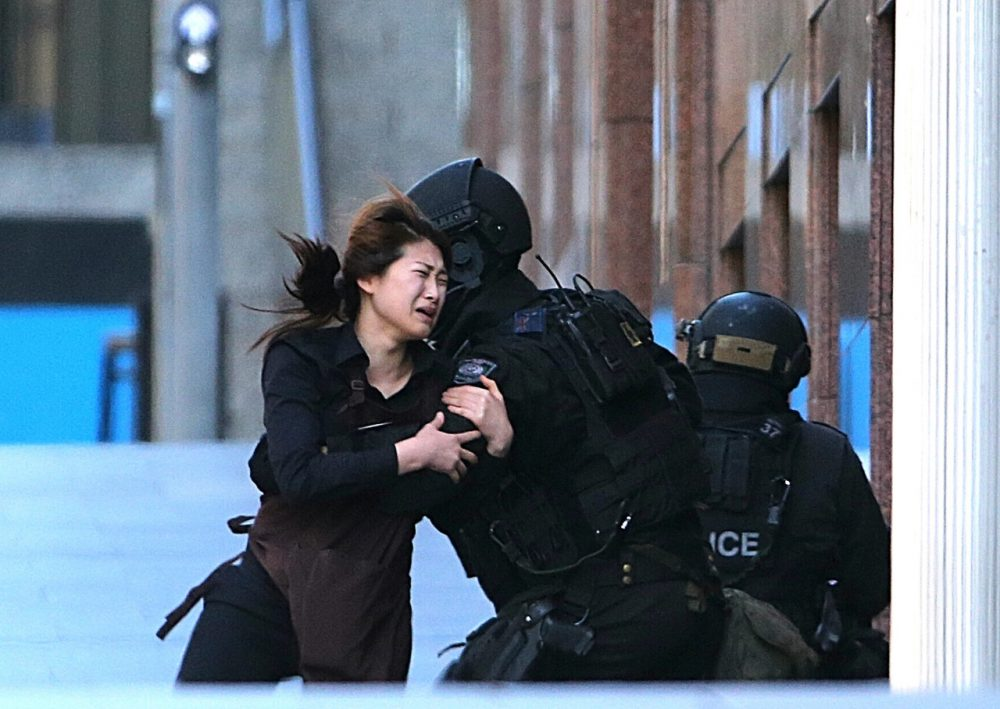 A hostage runs to armed tactical response police officers for safety after she escaped from a cafe under siege at Martin Place in the central business district of Sydney, Australia. (Rob Griffith/AP)