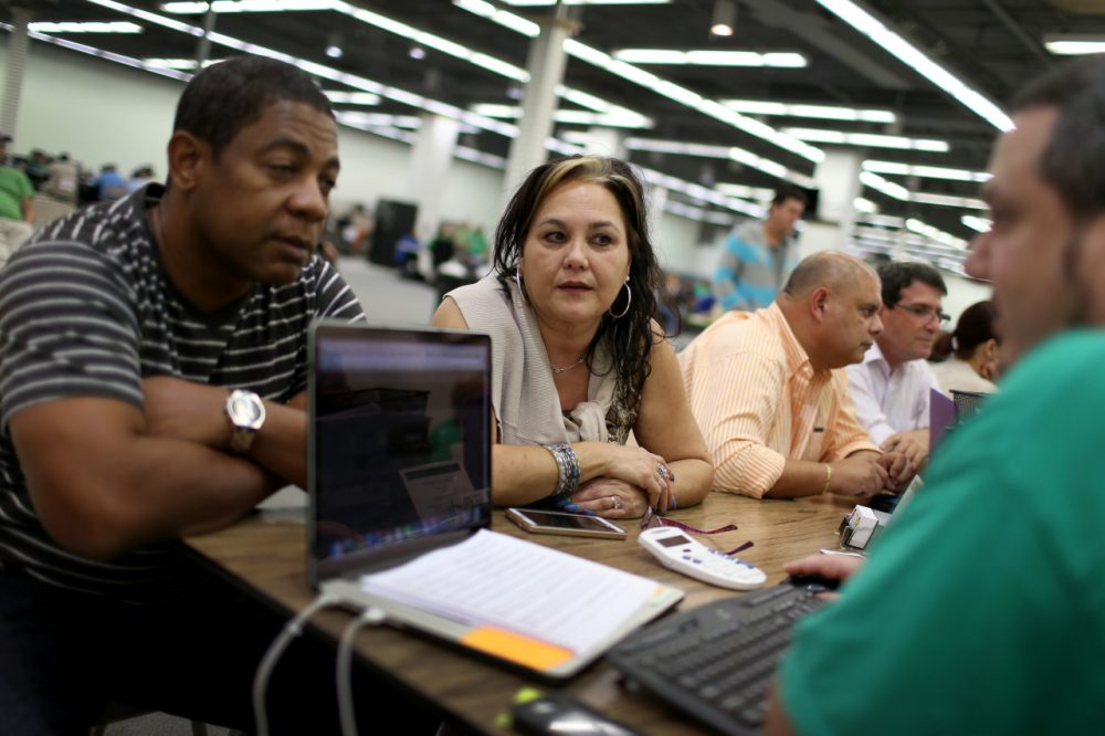 Jose Ramirez (left) and Mariana Silva speak with Yosmay Valdivia, an agent from Sunshine Life and Health Advisors, as they discuss plans available from the Affordable Care Act at a store setup in the Mall of the Americas on December 15, 2014 in Miami, Florida. (Joe Raedle/Getty Images)