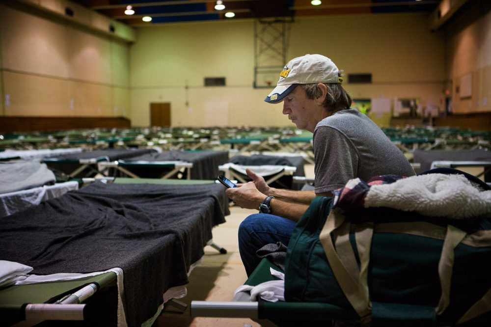 A man who did not want to be identified sits on a cot in a temporary shelter set up by the Boston Public Health Commission following the Long Island bridge closure. (Jesse Costa/WBUR)