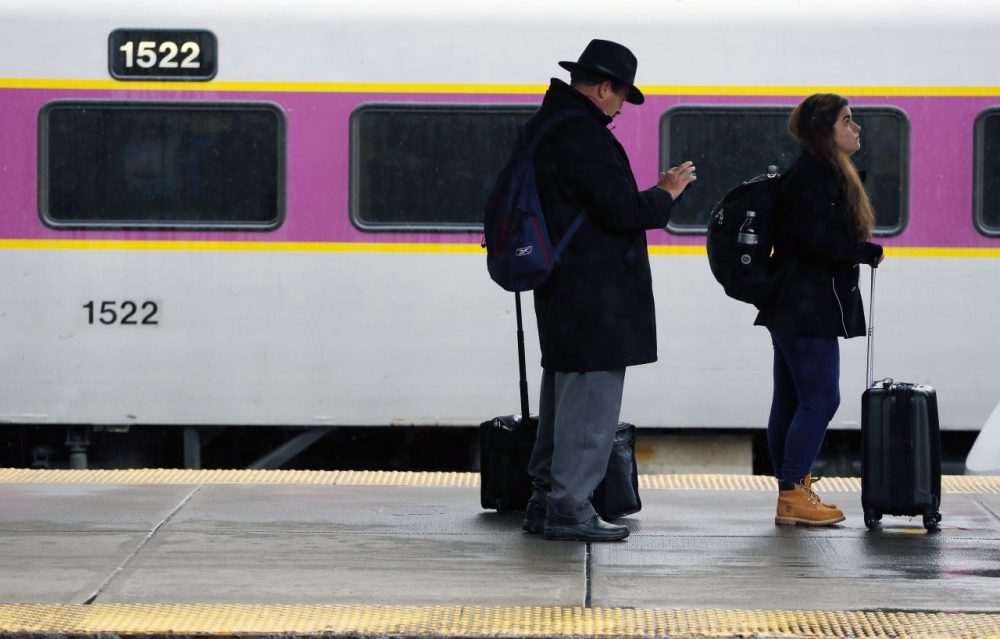 Passengers wait to board a train at South Station in Boston on Nov. 26. (Michael Dwyer/AP)