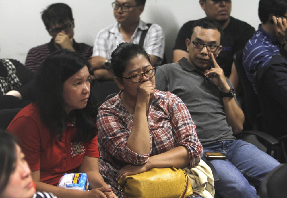 Relatives of the passengers of AirAsia flight QZ8015 wait for the latest news on the search of the missing jetliner at Juanda International Airport in Surabaya, East Java, Indonesia, Sunday (Trisnadi/AP)