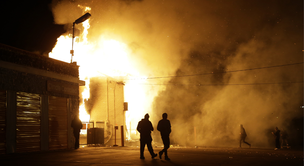 Reflecting on the heaviness of the top news stories of the year, and evaluating a common link between them. Pictured: Buildings on fire in Ferguson, Missouri after the announcement of the grand jury decision. (Jeff Roberson/AP)