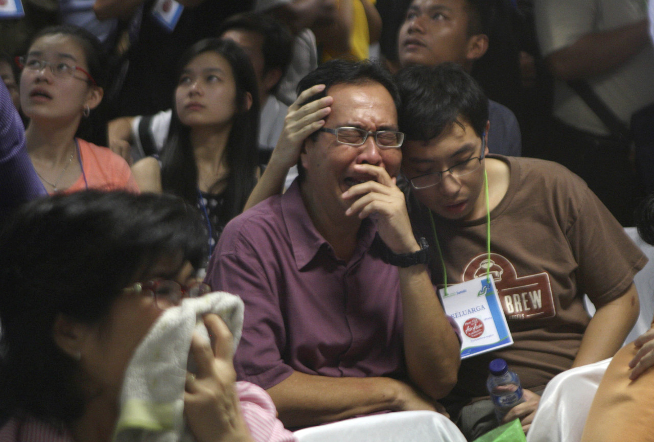 Relatives of passengers of the missing AirAsia Flight 8501 react upon seeing the news on television about the findings of bodies on the waters near the site where the jetliner disappeared. (Trisnadi/AP)