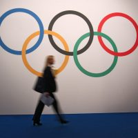 A woman walks in front of a board showing Olympics rings at the 127th International Olympic Committee session in Monaco, Monday, Dec. 8, 2014. (AP)