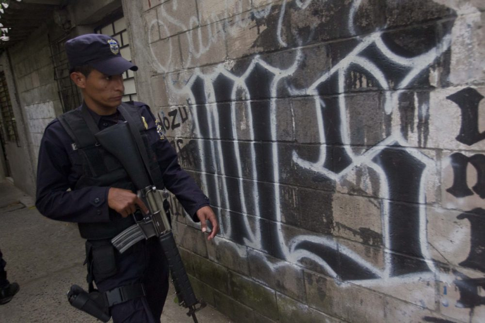 In this March 7, 2014 file photo, a member of the Salvadoran National Police walks next to graffiti of the Mara Salvatrucha gang painted on a wall during an anti-gang operation in San Salvador. Gang violence is prevalent in the Central American nation, and murders are up this year.
