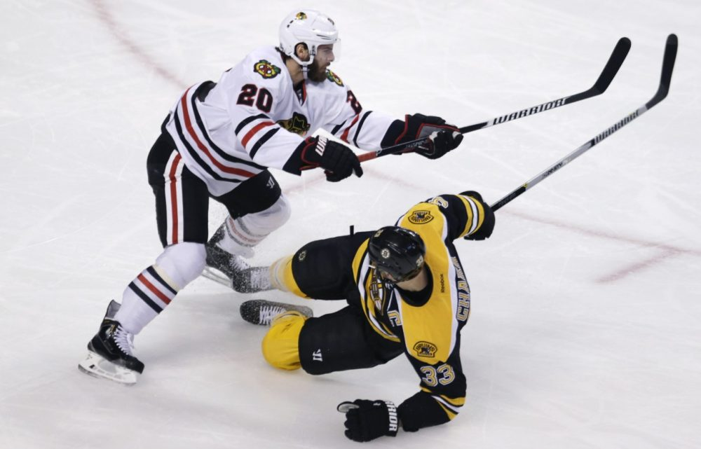 Chicago Blackhawks left wing Brandon Saad (20) drops Boston Bruins defenseman Zdeno Chara to the ice during the first period of Thursday, Dec. 11, 2014 game in Boston. Chara has been sidelined since October with a left knee injury. (Charles Krupa/AP)