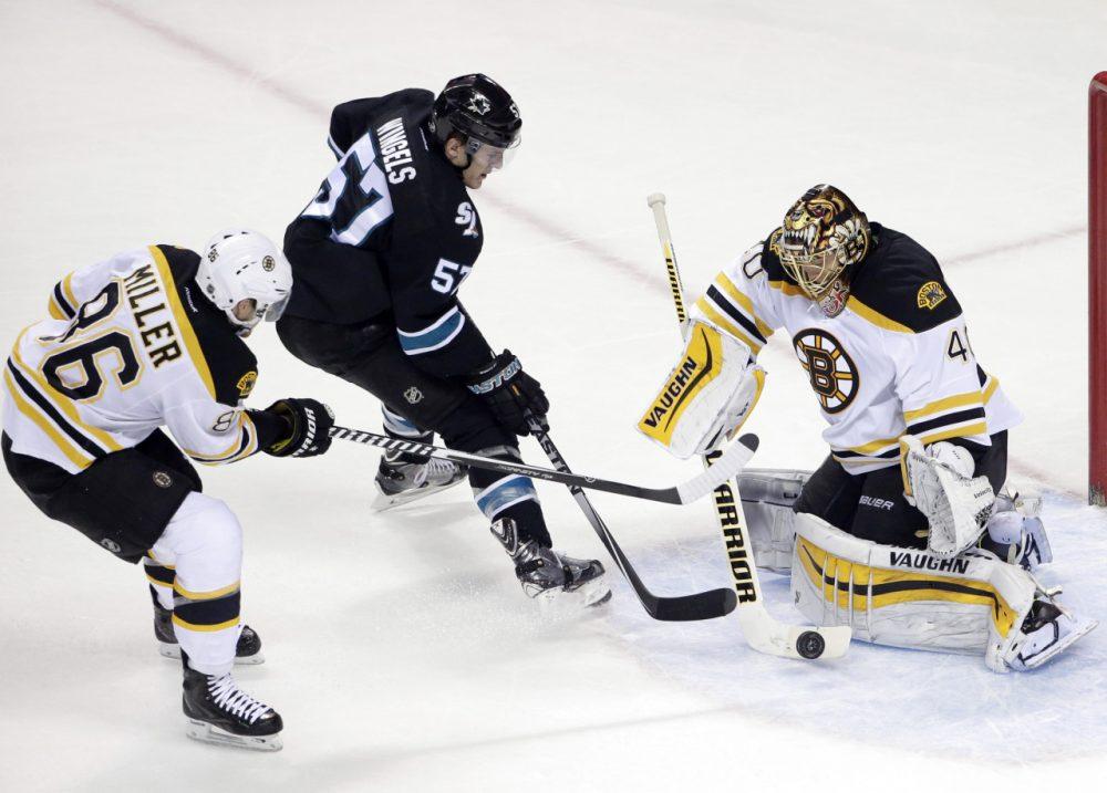 Boston Bruins goalie Tuukka Rask stops a shot from San Jose Sharks center Tommy Wingels  as Bruins defenseman Kevan Miller closes in. (Marcio Jose Sanchez/AP)