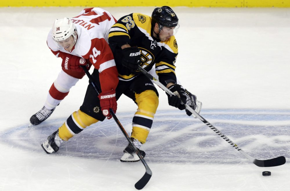 Boston Bruins left wing Brad Marchand (63) skates around Detroit Red Wings center Gustav Nyquist (14)  in Boston, Monday, Dec. 29, 2014. (Charles Krupa/AP)
