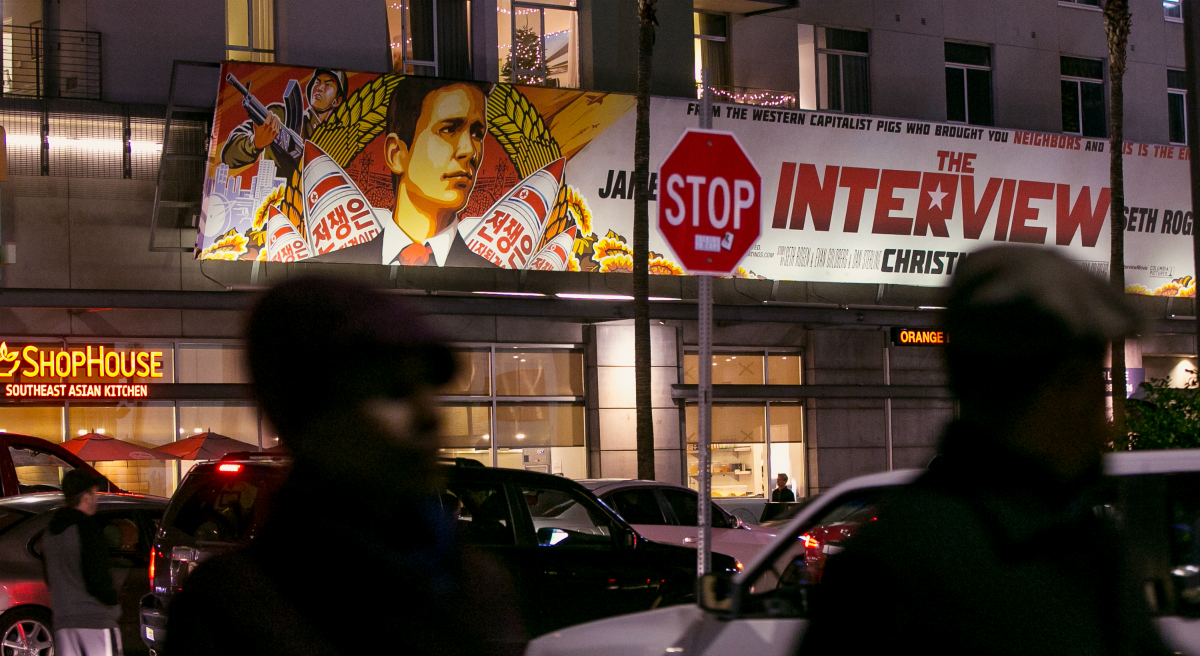 "People walk past a banner for ""The Interview""at Arclight Cinemas, Wednesday, Dec. 17, 2014, in the Hollywood section of Los Angeles. A U.S. official says North Korea perpetrated the unprecedented act of cyberwarfare against Sony Pictures that exposed tens of thousands of sensitive documents and escalated to threats of terrorist attacks that ultimately drove the studio to cancel all release plans for the film at the heart of the attack, ""The Interview."" (Damian Dovarganes/AP)"