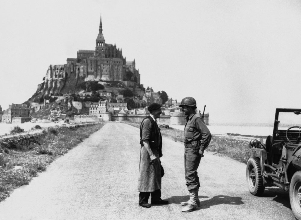 An American soldier and a French civilian chat on the causeway leading from the mainland of Brittany to the famous tourist resort of Mont St. Michel in Normandy on August 8, 1944. American forces in their advance across the peninsula seized the resort, which was undamaged. (HH/AP)