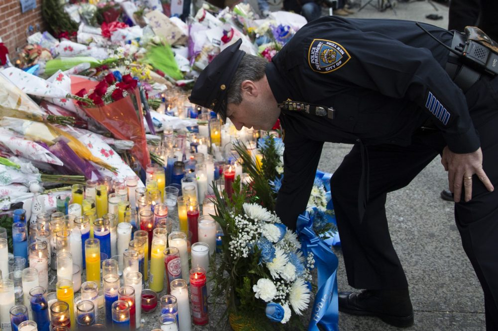 Patrick Lynch, president of the Patrolman's Benevolent Association, places flowers at a makeshift memorial on Monday near the site where NYPD officers Rafael Ramos and Wenjian Liu were murdered in Brooklyn. (Seth Wenig/AP)