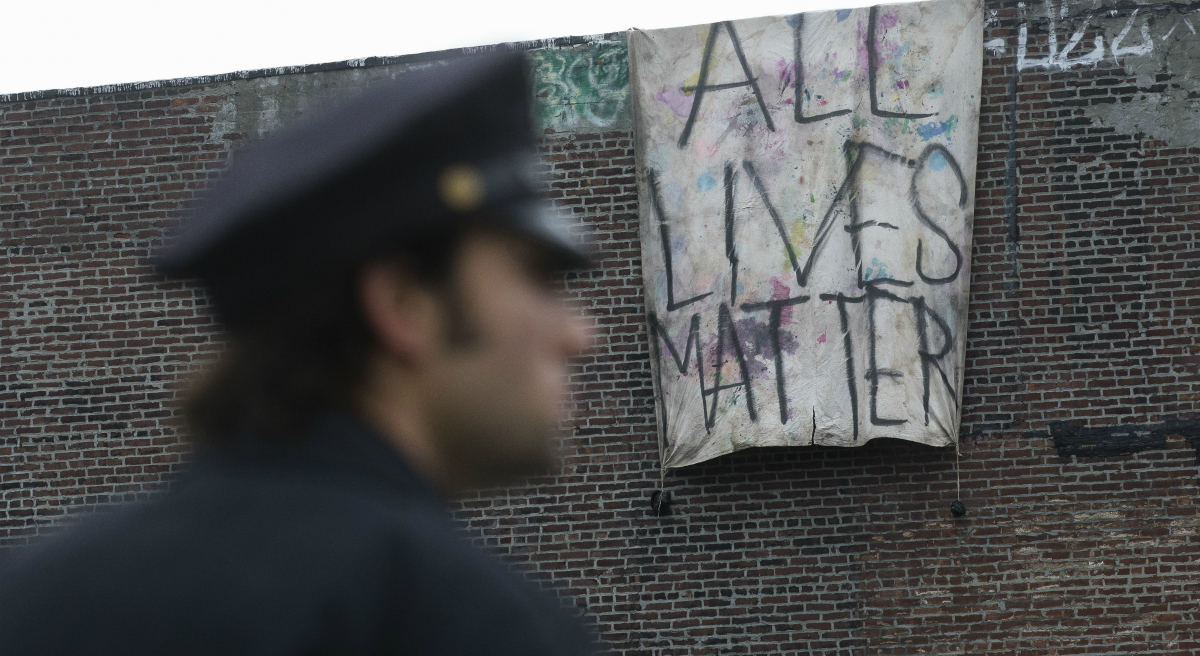 "A sign that reads ""ALL LIVES MATTER"" is hung from a building near a makeshift memorial at the site where NYPD officers Rafael Ramos and Wenjian Liu were murdered in the Brooklyn borough of New York, Monday, Dec. 22, 2014. Police say Ismaaiyl Brinsley ambushed the two officers in their patrol car in broad daylight Saturday, fatally shooting them before killing himself inside a subway station. (John Minchillo/AP)"