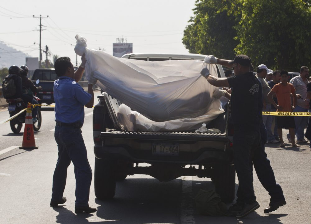 Forensic workers lift the body of an alleged gang member into the bed of a truck in San Salvador, El Salvador, on March 7, 2014. (Esteban Felix/AP)