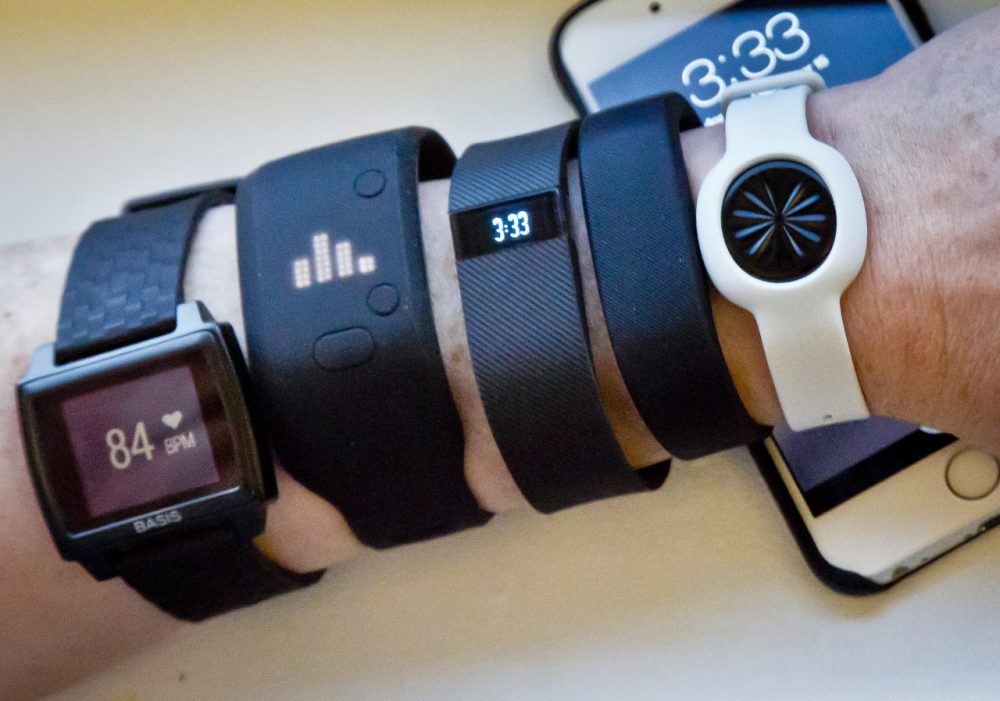 From left: Fitness trackers Basis Peak, Adidas Fit Smart, Fitbit Charge, Sony SmartBand and Jawbone Move are posed for a photo next to an iPhone in 2014. (Bebeto Matthews/AP)