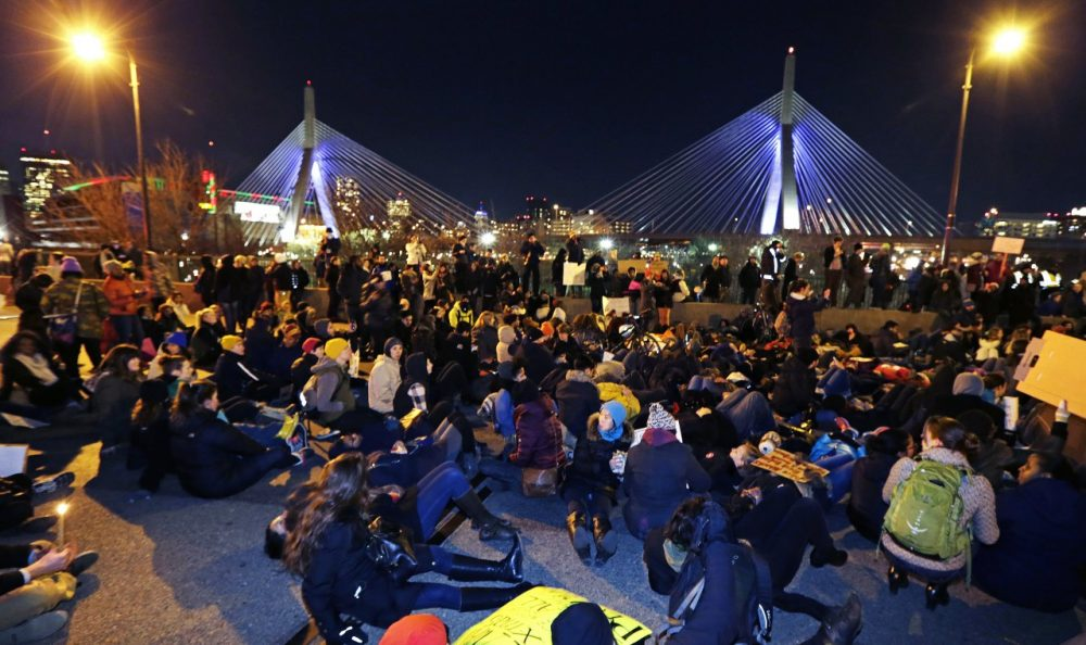 Thousands of protestors sit on the Charlestown Bridge blocking traffic into Downtown Boston during protests Thursday night. (Charles Krupa/AP)