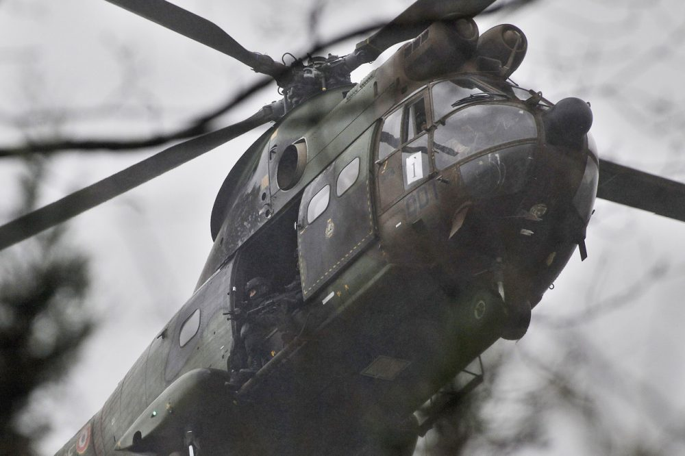 Armed security forces fly in a military helicopter in Dammartin-en-Goele on Friday. French security forces swarmed this small industrial town northeast of Paris in an operation to capture a pair of heavily armed suspects in the deadly storming of a satirical newspaper. (Thibault Camus/AP)
