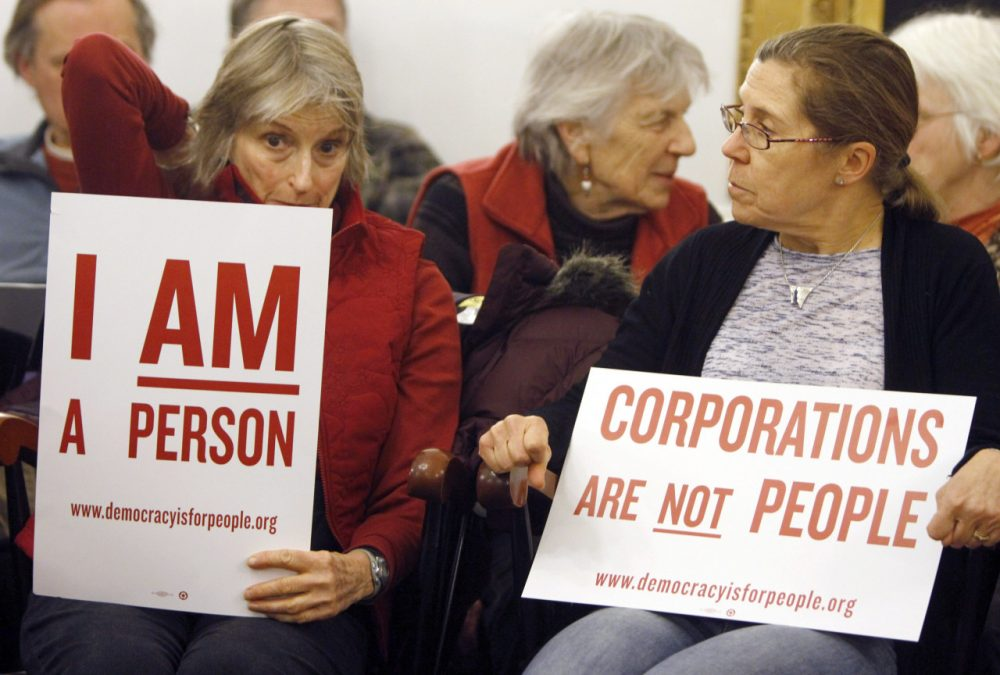 People hold signs during a gathering on the anniversary of the Citizens United decision in Montpelier, Vt. (Toby Talbot/AP)