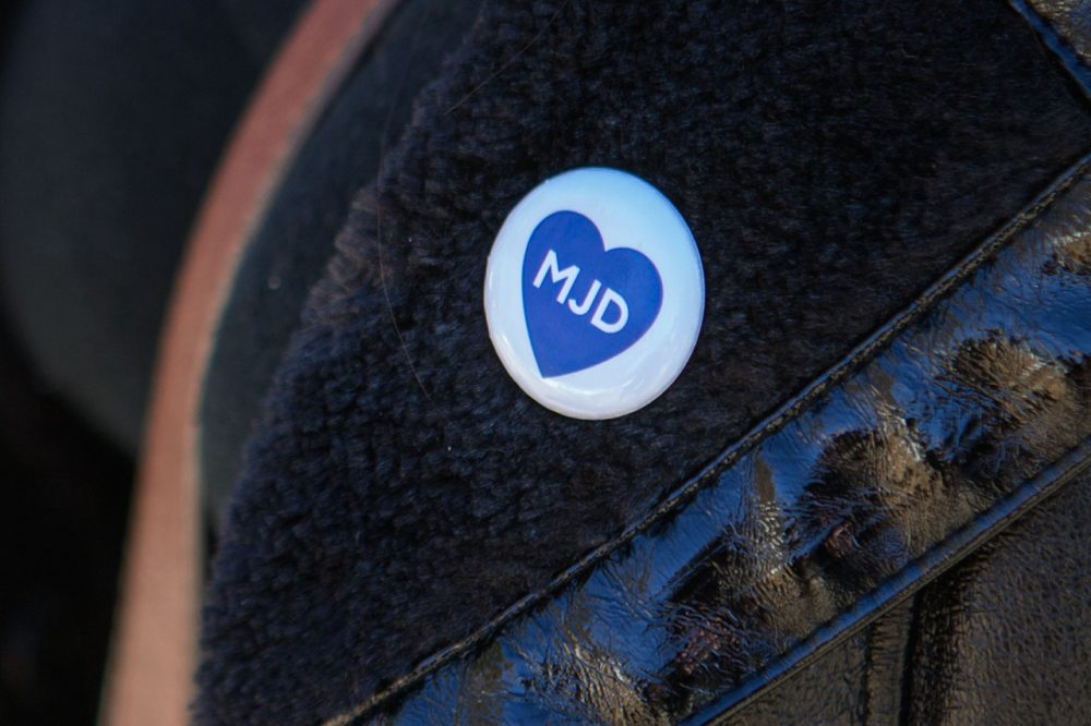 A woman wears a button honoring Michael Davidson at his funeral service Friday. (Jesse Costa/WBUR)