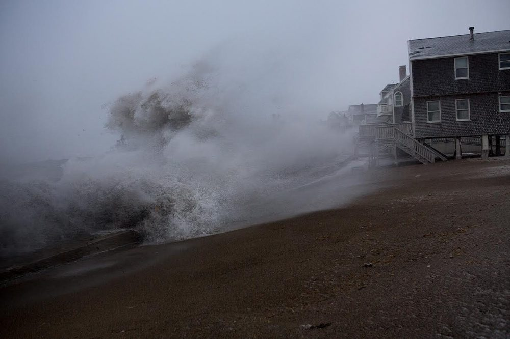 A wave crashes over the sea wall in the Cedar Point area of Scituate, during a January Nor'easter. (Jesse Costa/WBUR)