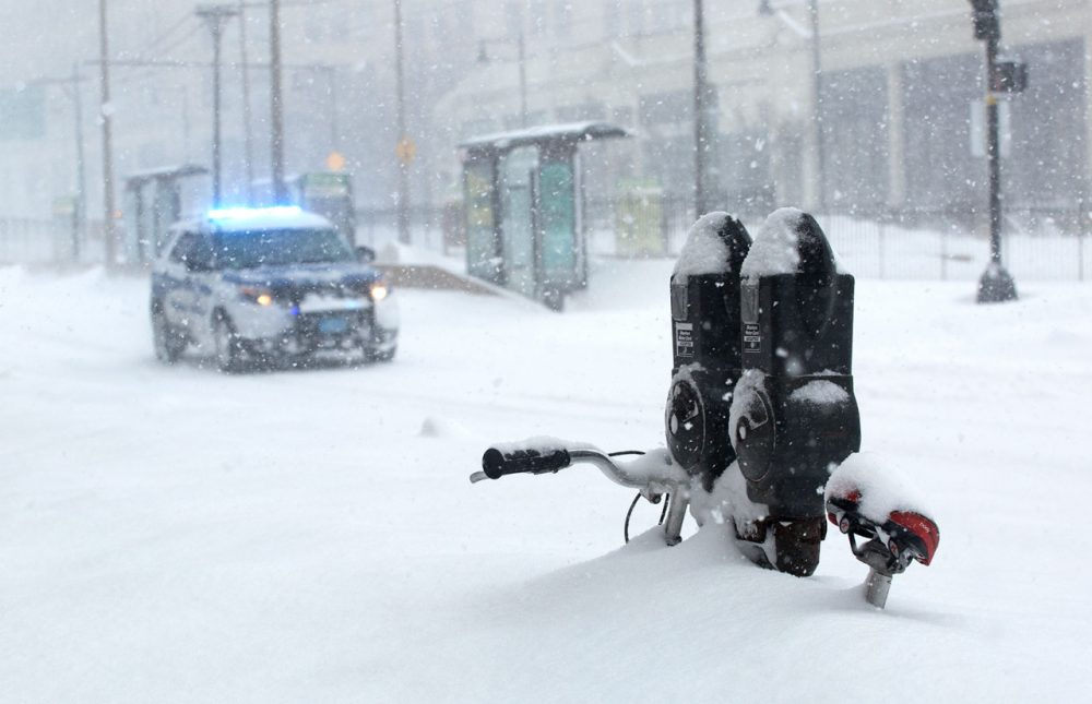 A police vehicle hurries down Commonwealth Avenue, past a bicycle and parking meter almost buried in snow. (Robin Lubbock/WBUR)