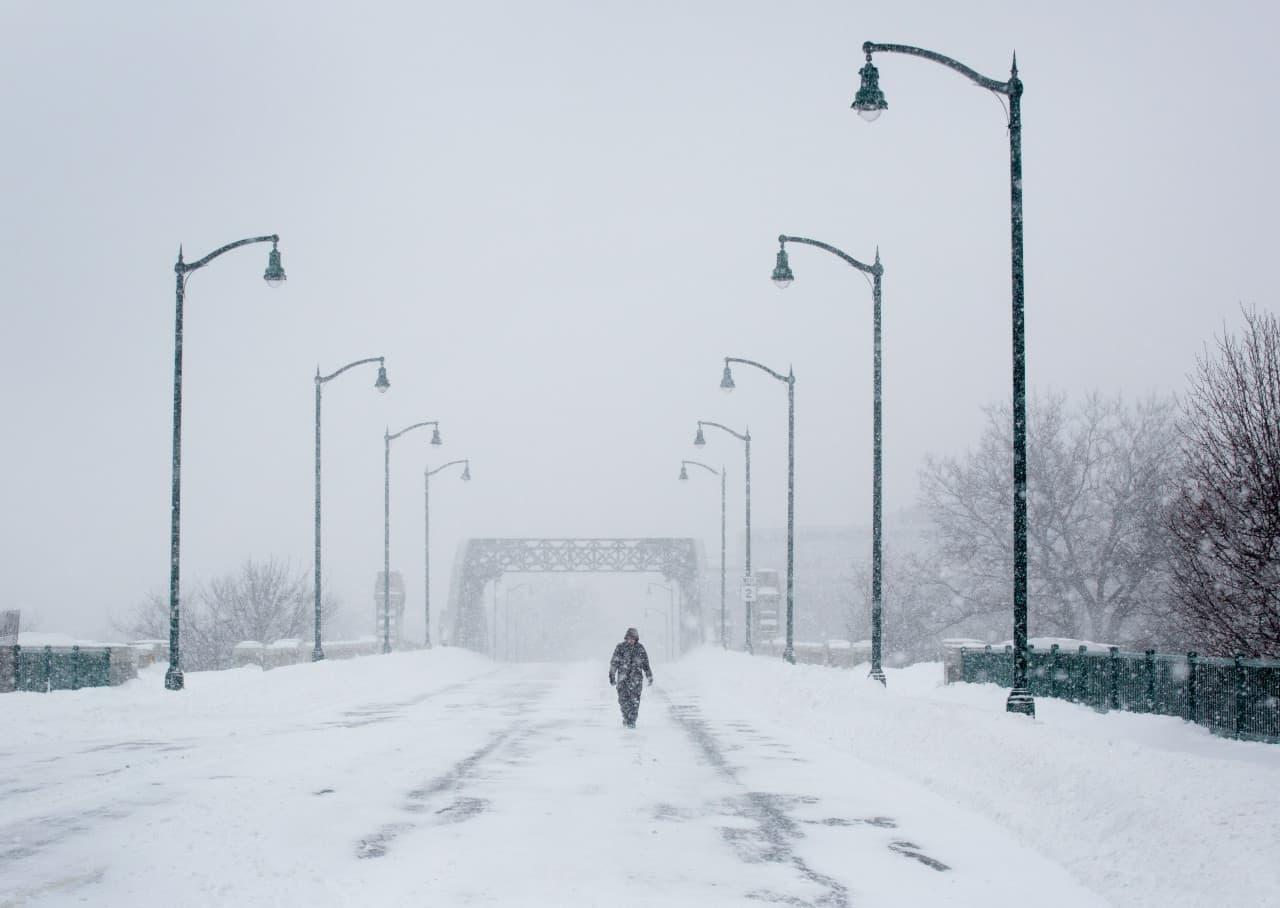 Jeff Way, a Harvard Medical School researcher, crossed the BU Bridge a snow continued to fall on Jan. 27, 2015. (Robin Lubbock/WBUR)