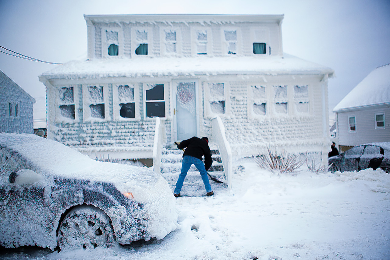Paul Rugg digs out of his sea-sprayed house on Foster Street in the Brandt Rock area of Marshfield. He had to climb out the window in order to open the front door. (Jesse Costa/WBUR)
