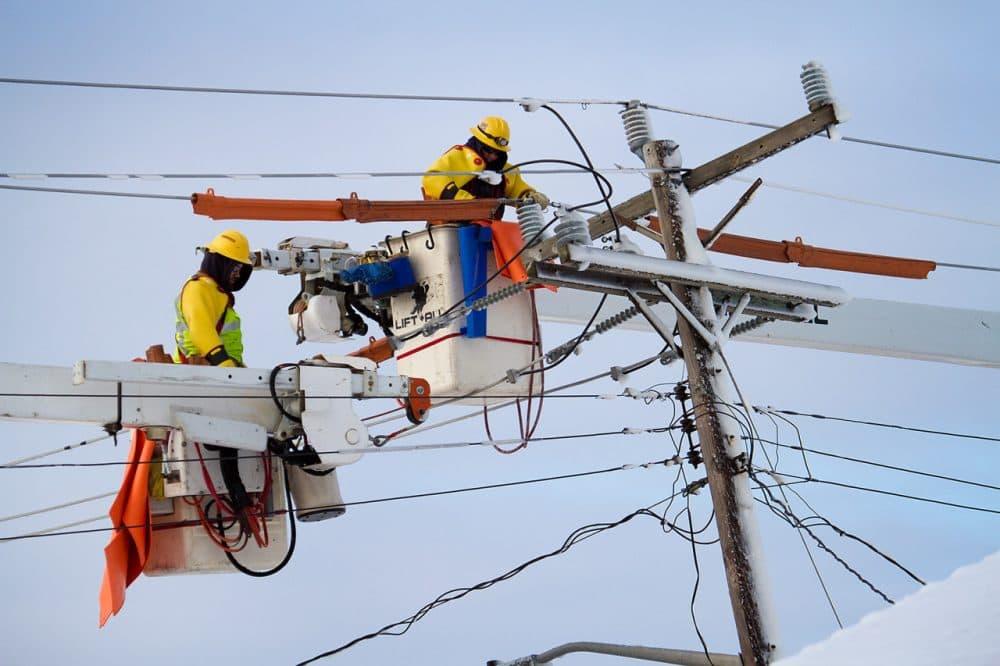 Workers from Western Mass Electric repair downed powerlines in Marshfield. (Jesse Costa/WBUR)