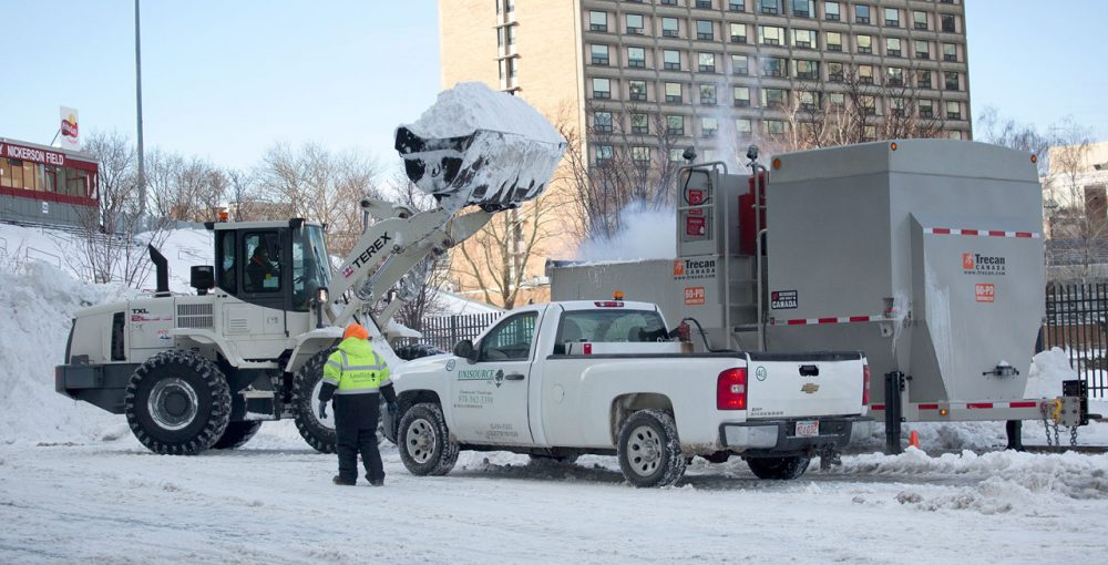 A loader piles snow into a snow melting machine on Harry Agganis Way by Boston University.   (Robin Lubbock/WBUR)