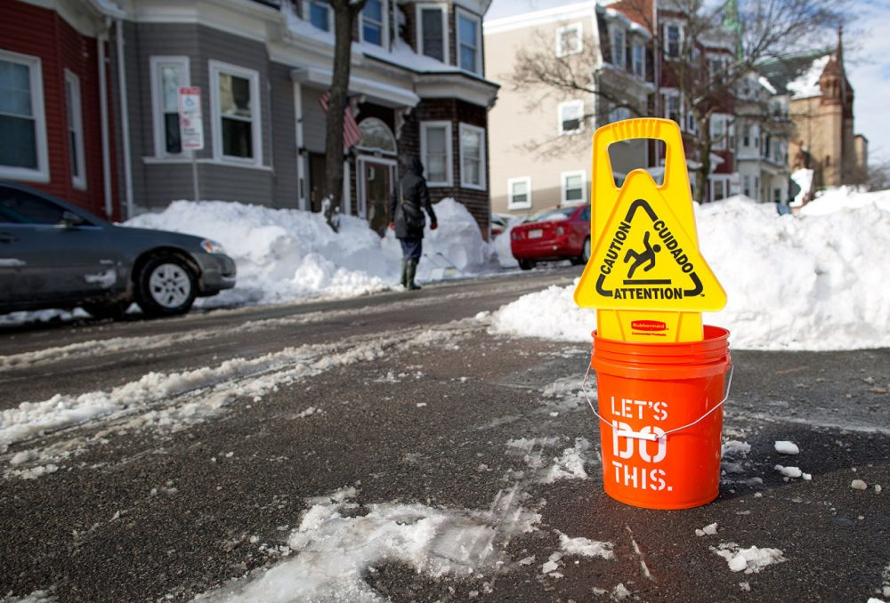 """Caution,"" and ""let's do this"" seem to send mixed messages to anyone eyeing this parking space on I St. in South Boston. (Robin Lubbock/WBUR)"