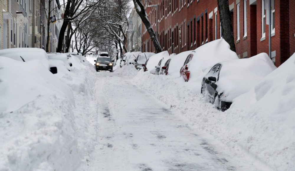 A car makes its way down a street filled with snowed-in vehicles in Boston's Charlestown section Wednesday. Gov. Baker announced a statewide travel ban as Monday's snowstorm got underway. (Elise Amendola/AP)