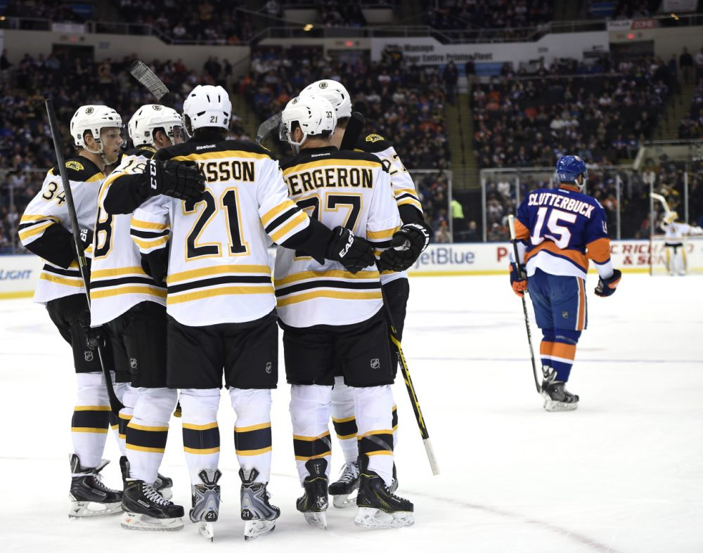 Boston Bruins center Patrice Bergeron (37) celebrates his goal with center Carl Soderberg (34), right wing Reilly Smith (18), left wing Loui Eriksson (21) and defenseman Dougie Hamilton (27) as New York Islanders right wing Cal Clutterbuck (15) skates away during Thursday night's game at Nassau Coliseum on Thursday, Jan. 29, 2015, in Uniondale, N.Y. (Kathy Kmonicek/AP)