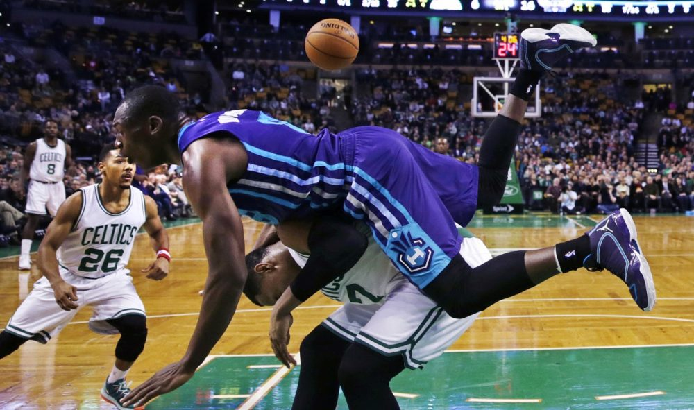 Charlotte Hornets center Bismack Biyombo, top, tumbles over Boston Celtics forward Jared Sullinger (7) on a rebound during Monday nights's game in Boston on Jan. 5, 2015. (Charles Krupa/AP)