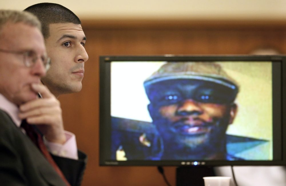 Aaron Hernandez listens during the first day of testimony in his murder trial Thursday. An image of Odin Lloyd, who Hernandez is charged with killing, is displayed on the monitor at right. (Steven Senne/AP)