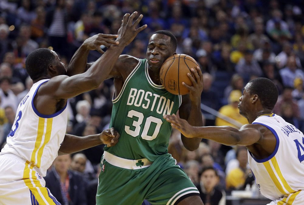 Boston Celtics' Brandon Bass (30) is guarded by Golden State Warriors' Draymond Green, left, and Harrison Barnes during Sunday night's game on Jan. 25, 2015, in Oakland, Calif. (Ben Margot/AP)