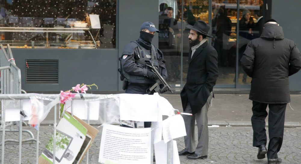 A police officer talks with a Jewish man outside the kosher grocery where Amedy Coulibaly killed four people in a terror attack, in Paris, Tuesday, Jan.20, 2015. Brothers Said and Cherif Kouachi and their friend, Amedy Coulibaly, killed 17 people at the satirical newspaper Charlie Hebdo, a kosher grocery and elsewhere. (Francois Mori/AP)