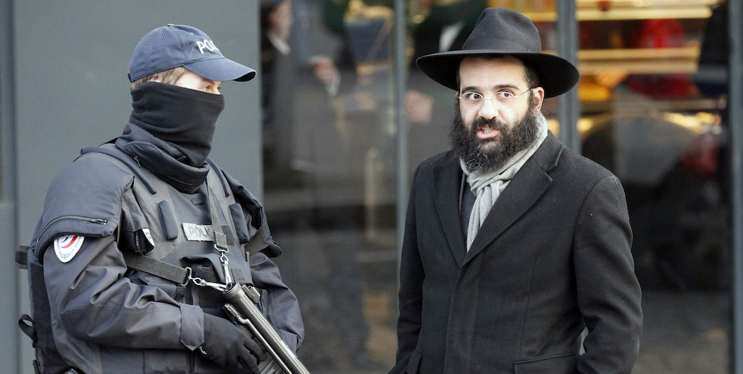 A police officer and a Jewish passerby talk outside the kosher grocery where four people were killed by Amedy Couiibaly.  (Francois Mori/AP)