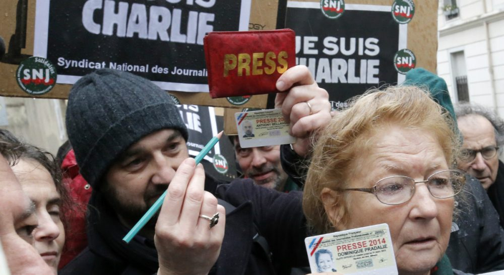 Journalists show their press cards and a pencil during a minute of silence outside the Charlie Hebdo newspaper in Paris, Thursday, Jan. 8, 2015, a day after masked gunmen stormed the offices of a satirical newspaper and killed 12 people. (François Mori/AP)