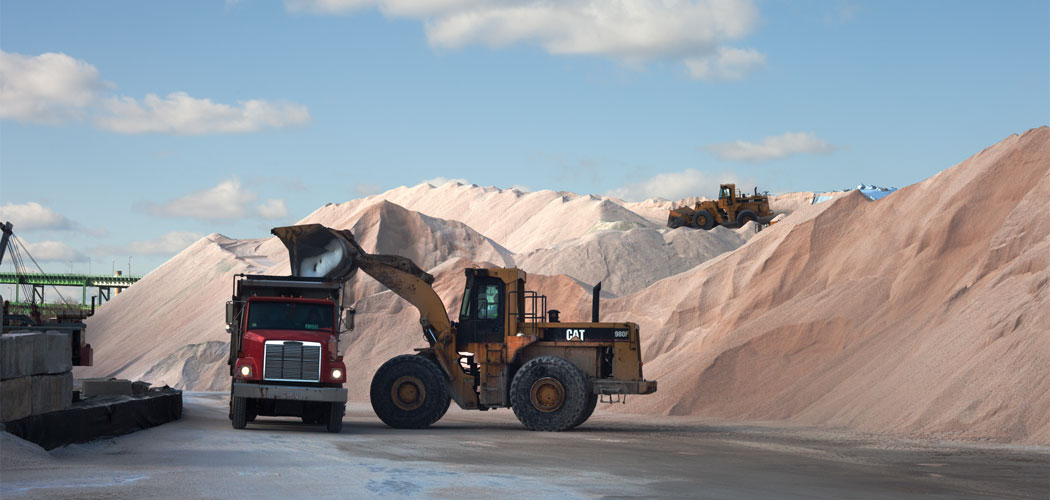 Front-end loaders at Eastern Salt Company in Chelsea fill dump trucks that carry the salt to municipal depots across the area. (Allison Cekala)