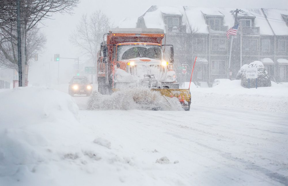 A snow plow works down Concord Avenue during the morning commute.
