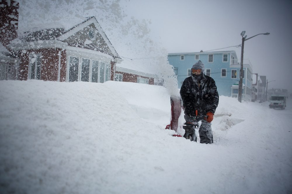 Sean Foley battles whiteout conditions while snowblowing his walkway in Winthrop. (Jesse Costa/WBUR)