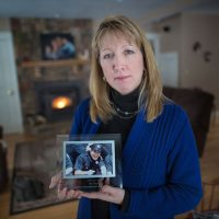 """Justine Barnes holds a photo of her brother, Lucas LaCaire. """"I don't hold back anymore. My brother died by suicide. My brother struggled,"""" Justine says. (Jesse Costa/WBUR)"""