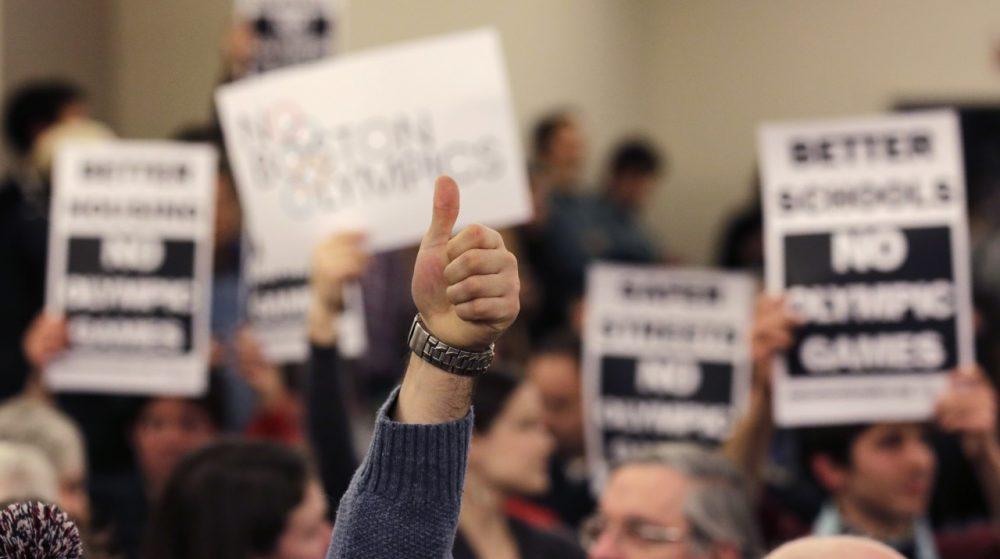 A supporter of the Boston Olympics bid gives a thumbs up in front of a group opposed to the bid, during the first public forum regarding the city's 2024 Olympics bid, on Thursday. (Charles Krupa/AP)