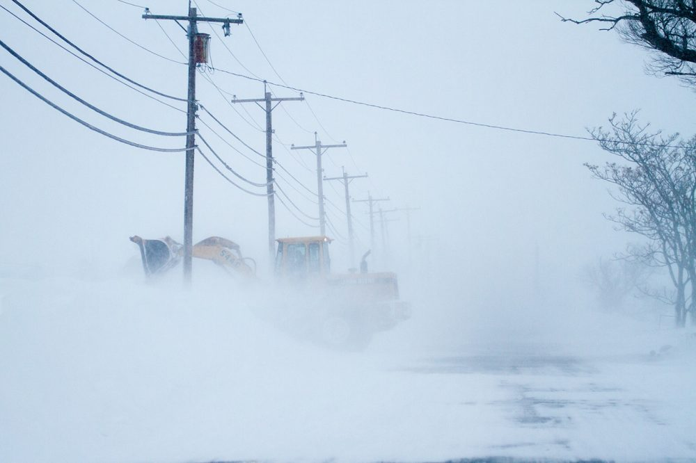 A land mover battles high winds moving snow off of the Plum Island Turnpike at Plum Island, in 2015. (Jesse Costa/WBUR/File)
