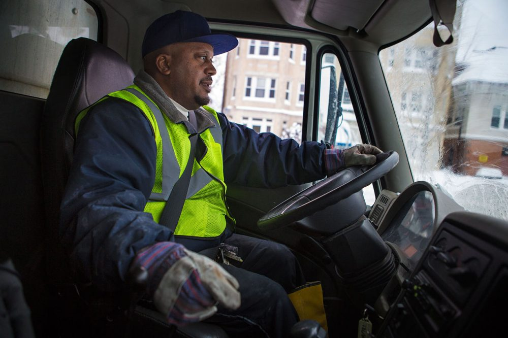 """City of Boston snow plow driver Erik McCormick was halfway through his 16-hour workday Tuesday when he picked up some WBUR tag-alongs. The days are long, he says, but """"we look forward to the snow. We call it white gold. We get a lot overtime during this time."""" (Jesse Costa/WBUR)"""